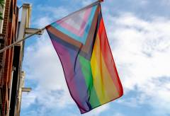 Progress pride flag (new design of rainbow flag) waving in the air with blue sky