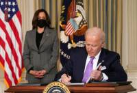 President Joe Biden signs papers with Vice President Kamala Harris in the background