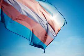 Transgender pride flag flying in front of blue sky
