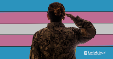 A person salutes in front of a transgender pride flag