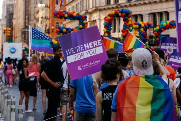 "Image of pride parade with person holding a sign reading ""we're here for you"""